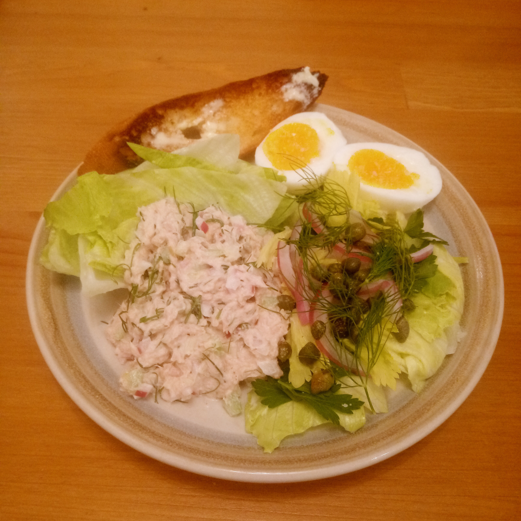 Plated tuna salad with lettuce leaves, toast, soft-boiled eggs, and an iceberg lettuce salad topped with parsley, celery leaves, sliced red onion, capers, and dill.